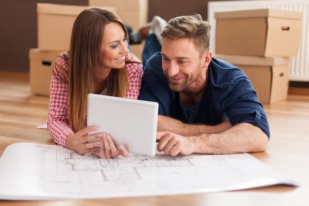 Paar, das neue wohnung mit digitalem tablett arrangiert
