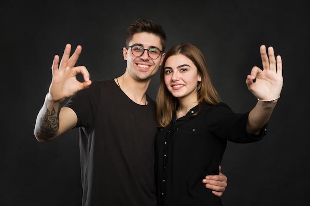 Paar, das ok-zeichen auf schwarzem hintergrund macht