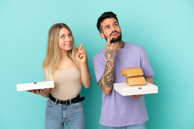 Paar, das pizza und burger über isoliertem blauem hintergrund hält, mit gekreuzten fingern und das beste wünscht