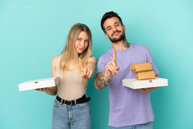 Paar, das pizza und burger über isoliertem blauem hintergrund hält und einen finger zeigt und hebt