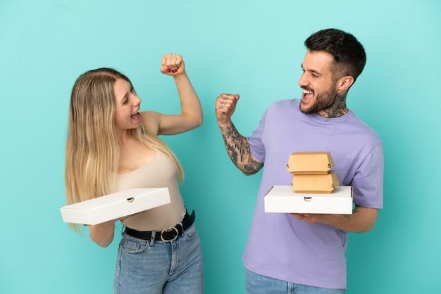 Paar, das pizza und burger über isoliertem blauem hintergrund hält und einen sieg in siegerposition feiert