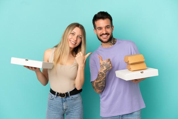 Paar, das pizza und burger über isoliertem blauem hintergrund hält und mit beiden händen eine daumen-hoch-geste gibt und lächelt