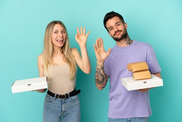 Paar, das pizza und burger über isoliertem blauem hintergrund hält und mit der hand mit glücklichem ausdruck grüßt