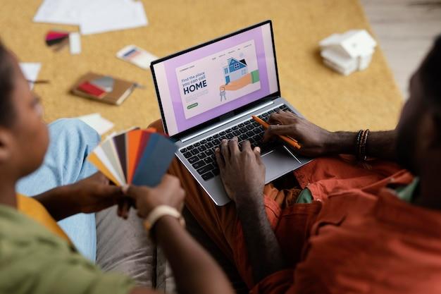 Paar, das pläne macht, haus mit farbpalette und laptop zu renovieren