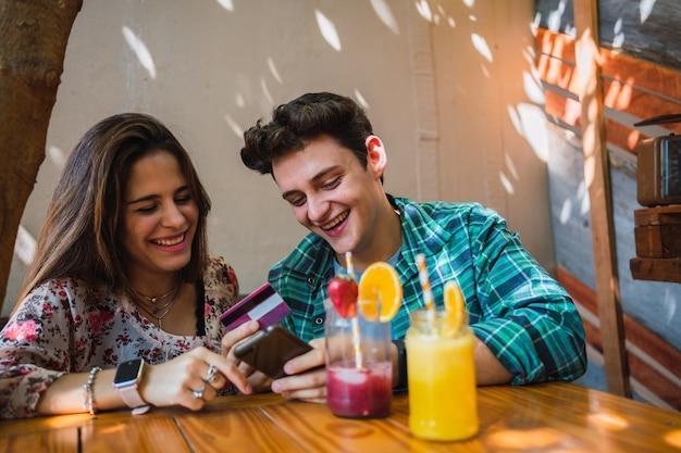 Paar, das rechnungen online mit smartphone und kreditkarte bezahlt.