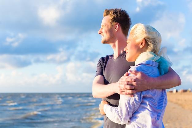Paar, das romantischen sonnenuntergang am deutschen nordseestrand genießt