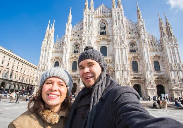 Paar, das selbstporträt auf dem domplatz in mailand nimmt. reise- und beziehungskonzept