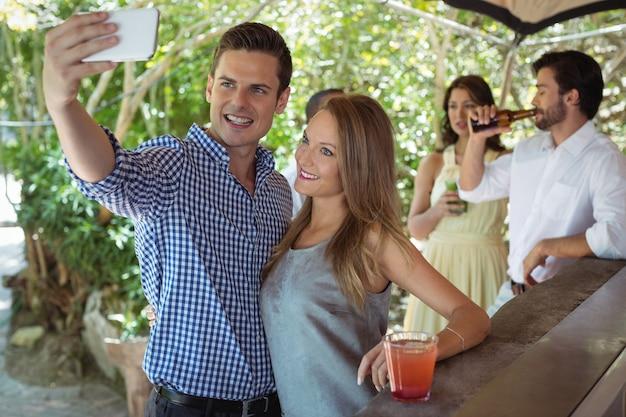 Paar, das selfie nimmt, während cocktail an der theke hat