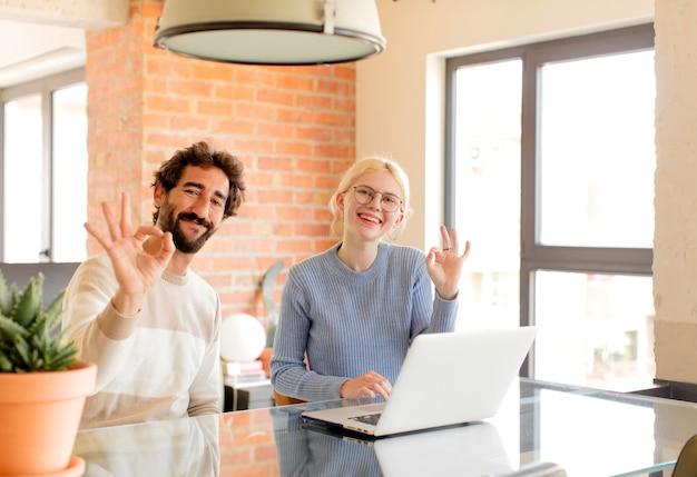 Paar, das sich glücklich, entspannt und zufrieden fühlt, zustimmung mit einer okayen geste zeigt, lächelt