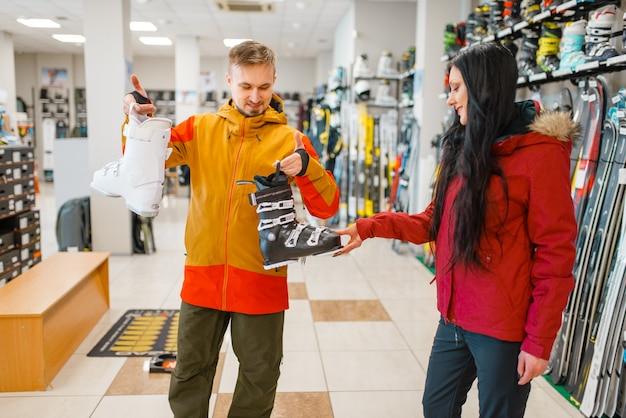 Paar, das ski- oder snowboardschuhe wählt, einkaufen im sportgeschäft. extremer lebensstil in der wintersaison, aktives freizeitgeschäft, kunden, die skiausrüstung kaufen