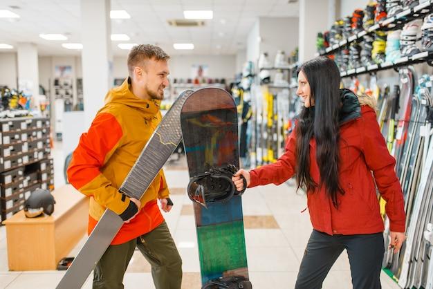 Paar, das skifahren und snowboard kauft, einkaufen im sportgeschäft.