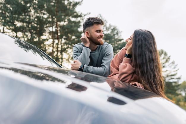 Paar, das spaß hat, auf auto stehend zu sprechen