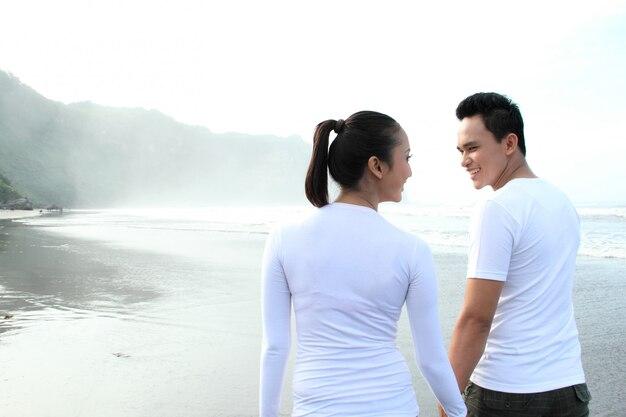 Paar, das spaß hat, einen sommerurlaub am strand zu genießen