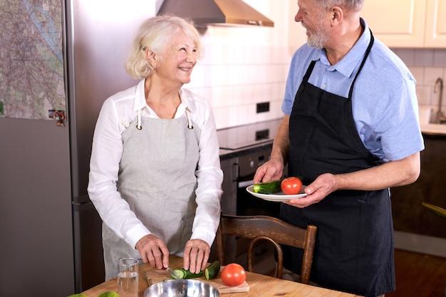 Paar, das spaß in der küche mit gesundem essen hat, essen zu hause kocht, mittagessen mit biologisch frischem gemüse zubereitet, gemüse schnitzt oder schneidet, mann hilft seiner frau, schürze tragend
