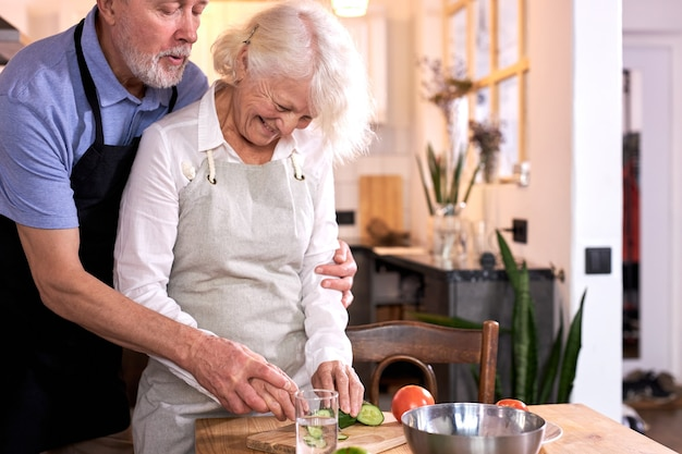 Paar, das spaß in der küche mit gesundem essen hat, mahlzeit zu hause kocht, mittagessen mit biologisch frischem gemüse zubereitet, gemüse schnitzt oder schneidet, mann hilft seiner frau, schürze tragend