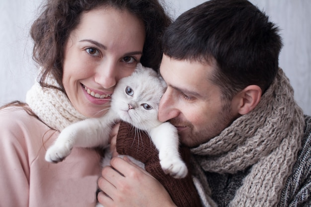 Paar, das spielt mit haustier katze zu hause spielt