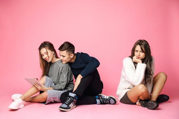Paar, das tablette und traurige frau betrachtet, die auf rosa boden sitzt