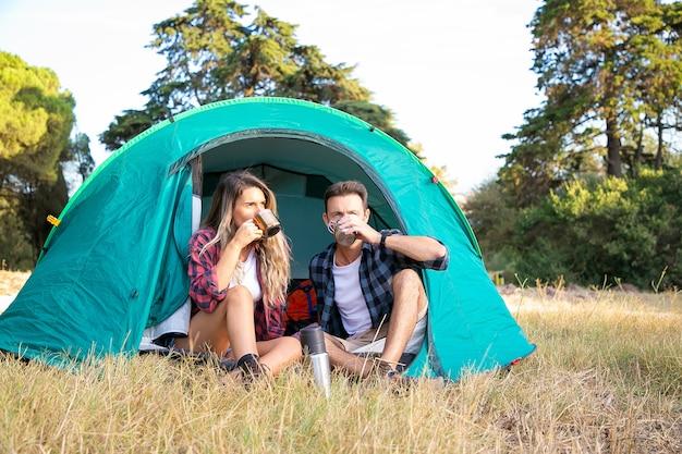 Paar, das tee trinkt und naturlandschaft betrachtet. attraktive kaukasische touristen, die sich im zelt entspannen, die landschaft genießen und auf dem rasen sitzen. backpacking tourismus, abenteuer und sommerurlaub konzept