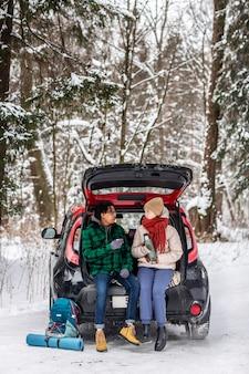 Paar, das tee trinkt, während auf autokofferraum sitzt