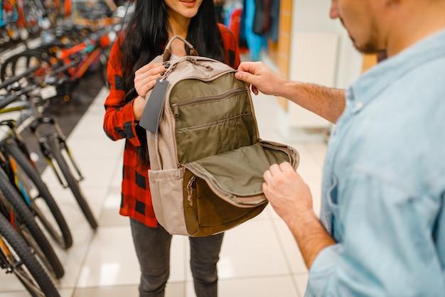 Paar, das touristische ausrüstung für reisen, einkaufen im sportgeschäft wählt. extremer lebensstil der sommersaison, aktives freizeitgeschäft, kunden, die rucksack kaufen