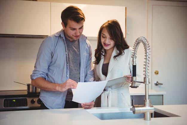 Paar, das über digitales tablett in der küche diskutiert