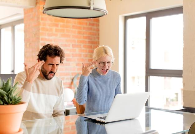 Paar, das unglücklich und gestresst aussieht, selbstmordgeste, die waffenzeichen mit der hand macht und auf den kopf zeigt