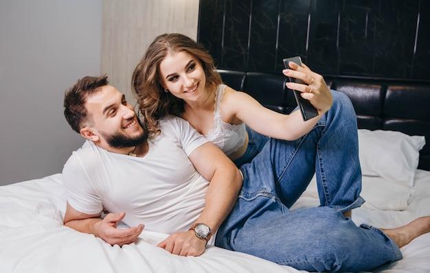 Paar, das video-chat mit freunden im bett zu hause hat