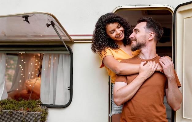 Paar, das vor wohnmobil steht und sich ansieht