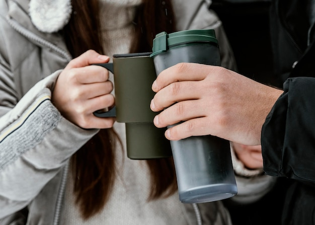 Paar, das während eines road trips ein warmes getränk im kofferraum des autos trinkt