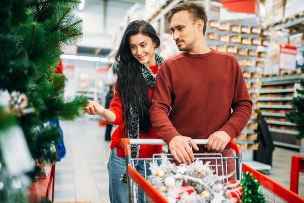 Paar, das weihnachtsbaum im supermarkt kauft