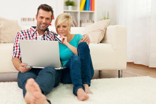Paar, das zu hause auf teppich sitzt und online einkauft