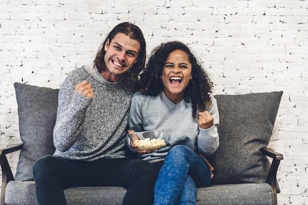 Paar, das zusammen popcorn isst und fernsieht