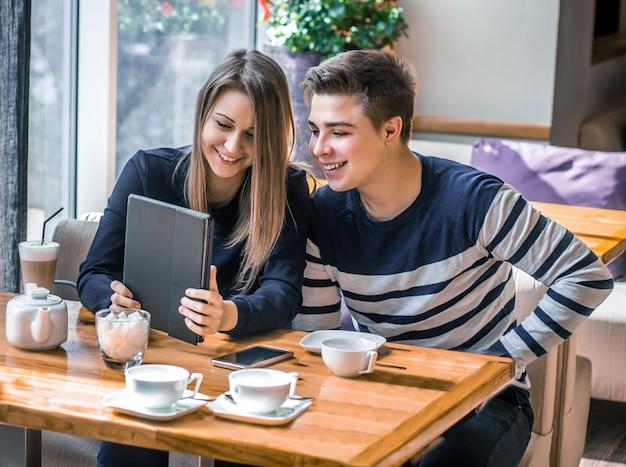 Paar-dating in einem café sie haben spaß und lächeln mit tablet-dating-liebe