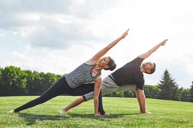 Paar dehnt sich junges paar aus und macht yoga-übungen in der natur an einem sonnigen morgen