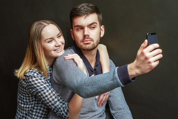 Paar der blonden frau und des bärtigen mannes, der selfie gegen schwarzen hintergrund macht. studioaufnahme