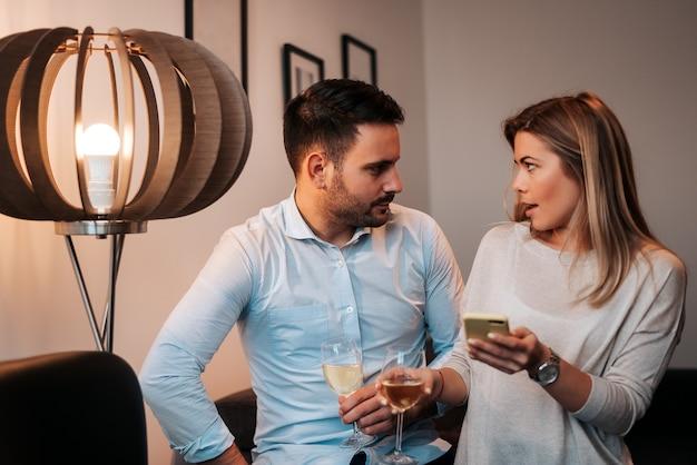 Paar diskutieren etwas zu hause. weißwein trinken.
