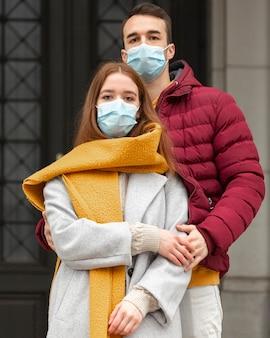 Paar draußen mit medizinischen masken