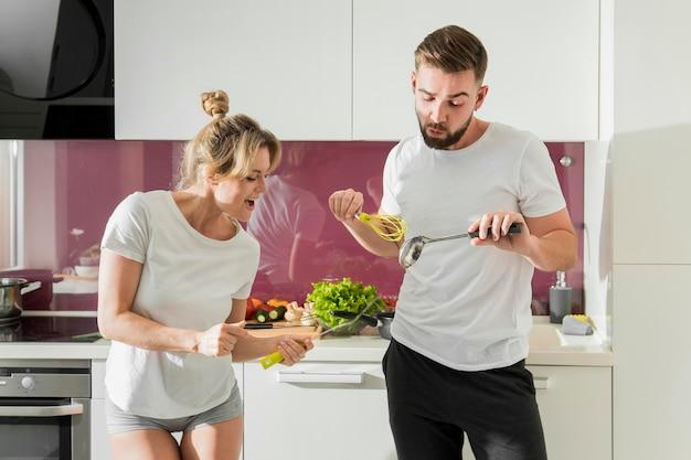 Paar drinnen, das das essen zubereitet