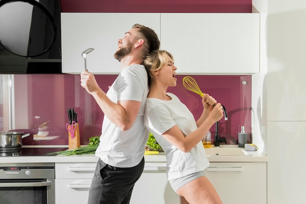 Paar drinnen, das in der vorderansicht der küche singt
