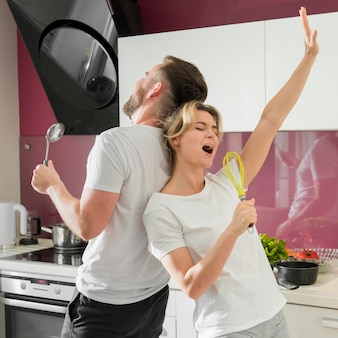 Paar drinnen, das zusammen in der küche singt