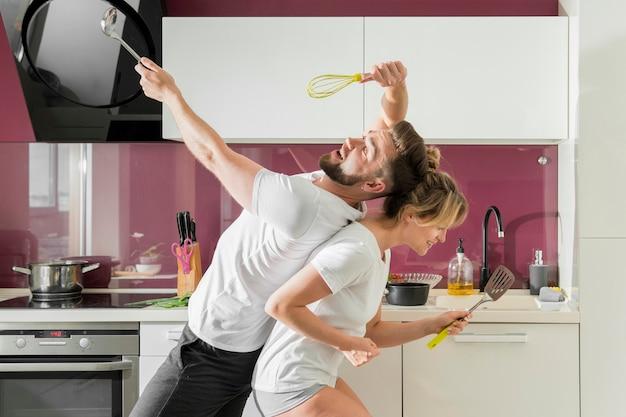 Paar drinnen singend in der küche, die in der seitenansicht sitzt