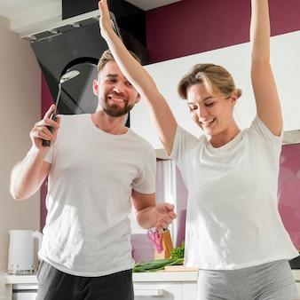 Paar drinnen tanzen in der küche zusammen