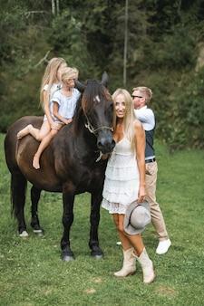Paar, ehemann und ehefrau, streichelt braunes pferd mit vergnügen im glänzenden sonnenlicht im sommer