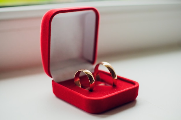Paar eheringe aus weißgold mit diamanten im damenring. silberne eheringe mit edelsteinen auf minimalistischem grauem hintergrund mit schatten.