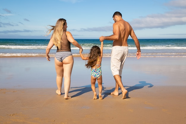 Paar eltern und kleine tochter, die badeanzüge tragen und auf goldenem sand zum wasser gehen
