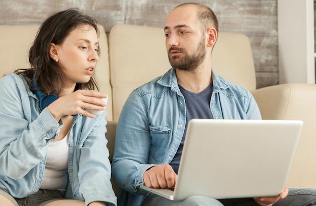 Paar entspannt sich im wohnzimmer, trinkt kaffee und surft im internet?