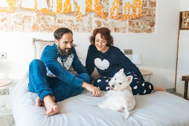 Paar entspannt zu hause im bett mit dem hund