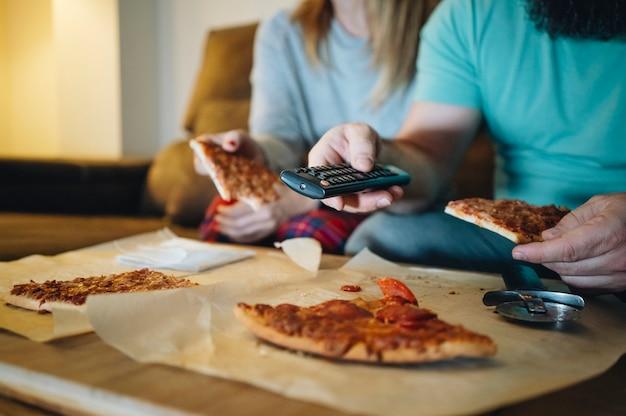 Paar essen pizza auf dem sofa in ihrem wohnzimmer in der nacht, während sie einen film im fernsehen sehen.
