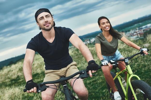 Paar fährt fatbikes nacheinander bewölkter himmel