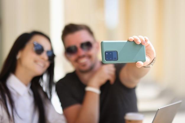 Paar fotografieren sich am telefon.